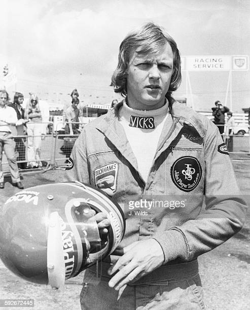 Swedish racing driver Ronnie Peterson, driver for the John Player Specials, pictured holding his helmet after a practice session for the British...
