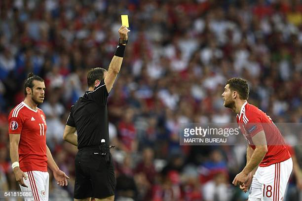 Swedish referee Jonas Eriksson gives a yelow card to Wales' forward Sam Vokes as Wales' forward Gareth Bale looks on during the Euro 2016 group B...