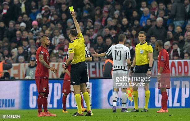 Swedish referee Jonas Eriksson shows a yellow card to Bayern Munich's Chilean midfielder Arturo Vidal during the UEFA Champions League Round of 16...