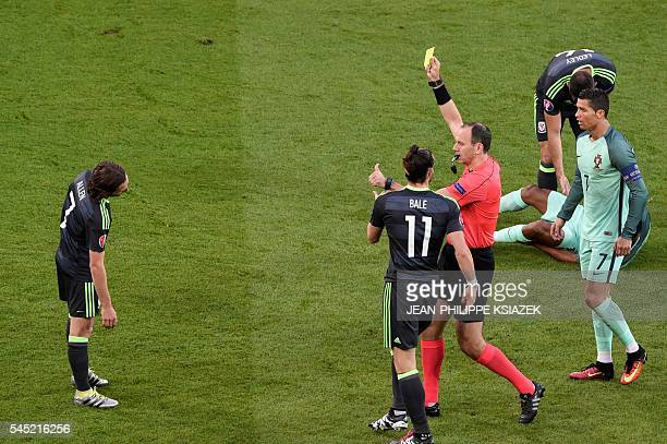 Swedish referee Jonas Eriksson shows a yellow card to Wales' midfielder Joe Allen for a foul on Portugal's forward Nani during the Euro 2016...