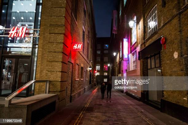 swedish retail-clothing company hennes & mauritz (h&m) and people on city street in london, uk - modern essentials by h&m stock pictures, royalty-free photos & images