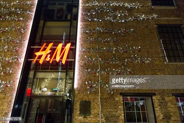 swedish retail-clothing company hennes & mauritz (h&m) on city street in london, uk - modern essentials by h&m stock pictures, royalty-free photos & images
