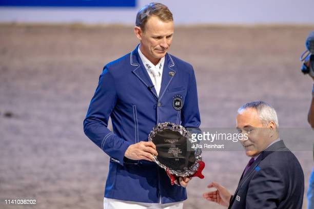 Swedish rider Peder Fredricson receives his third place trophy of FEI President Ingmar De Voss during the price giving ceremony for the 2019 Longines...