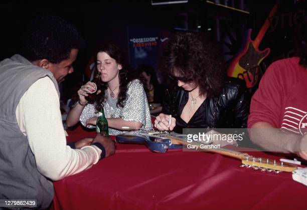 Swedish Rock and Heavy Metal musician Yngwie Malmsteen autographs an electric guitar for a fan at Tower Records in the neighborhood of Greenwich...