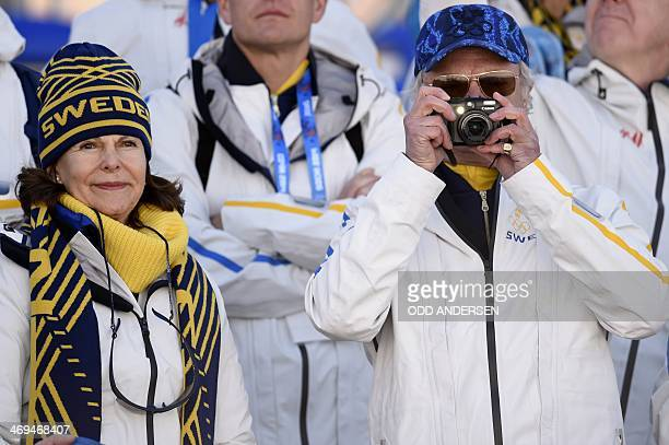 Swedish royals King Carl XVI Gustaf and Queen Silvia watch as Sweden's Gold Medallist relay team goes to the podium during the Women's CrossCountry...