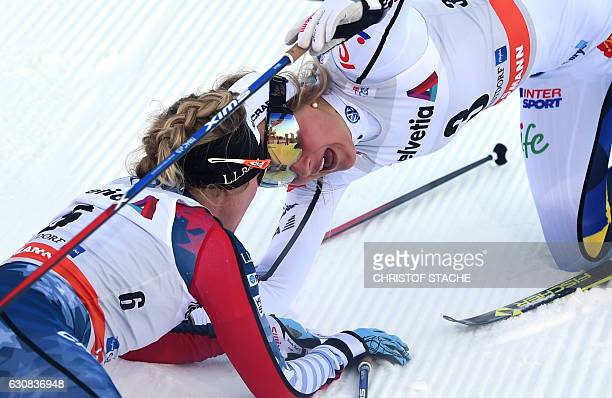 """Swedish Stina Nilsson reacts with US Jessica Diggins after she passed the finish line of the ladies 5 kilometer skiathlon competition of the """"Tour de..."""