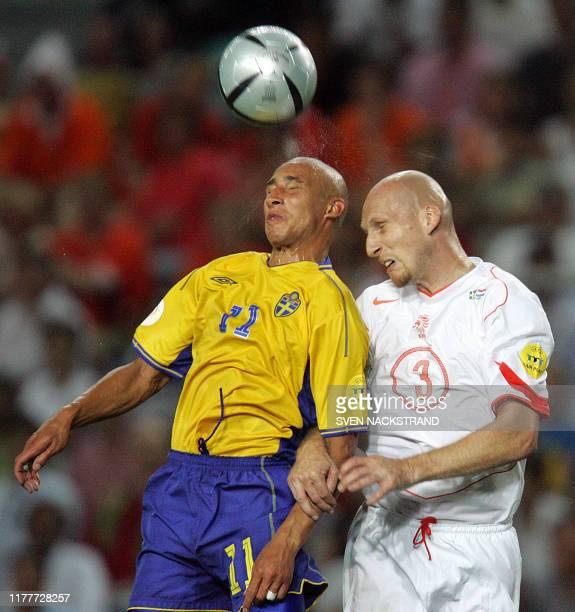 Swedish striker Henrik Larsson heads the ball next to Dutch defender Jaap Stam 26 June 2004 at the Algarve stadium in Faro during the Euro 2004...