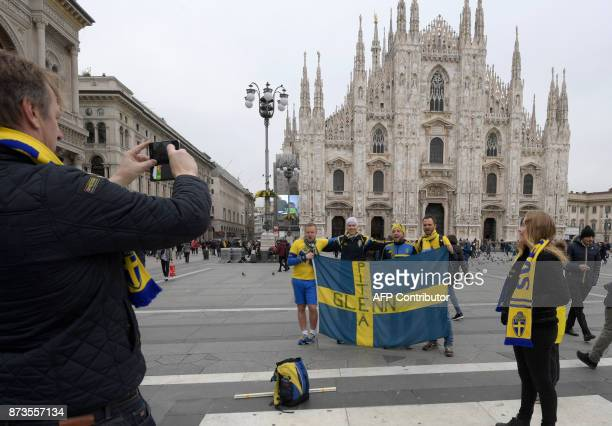 Swedish supporters pose for pictures at Piazza del Duomo on November 13 2017 in Milan prior the FIFA World Cup 2018 qualification football match...