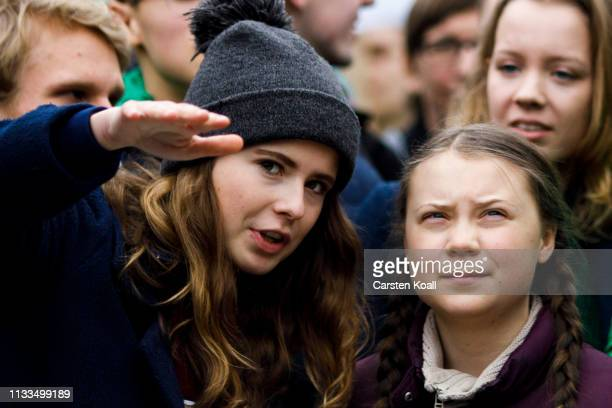 Swedish teenage climate activist Greta Thunberg speaks with German climate activist Luisa Neubauer as they participate in a Fridays for Future march...