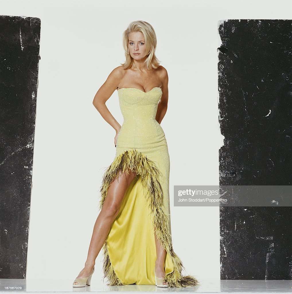 Swedish television presenter Ulrika Jonsson poses in a yellow dress, 1997.
