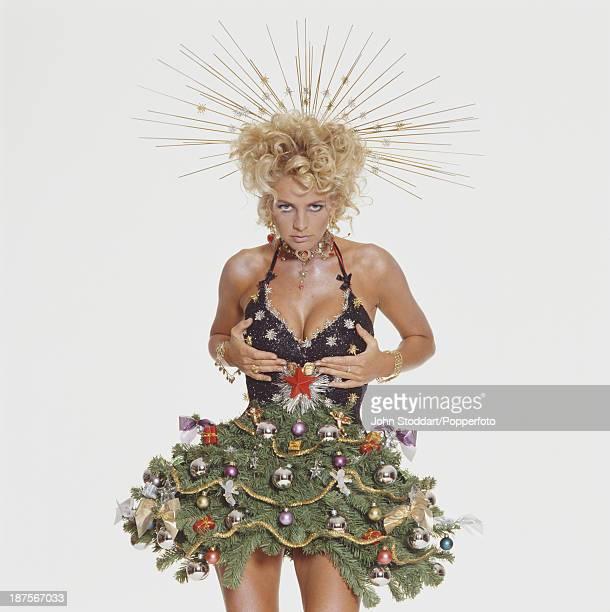 Swedish television presenter Ulrika Jonsson poses wearing Christmas decorations circa 1998