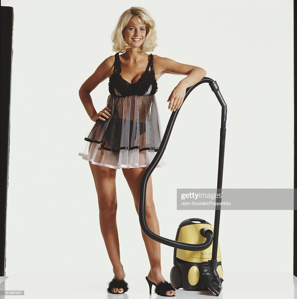 Swedish television presenter Ulrika Jonsson poses with a vacuum cleaner, 1996.