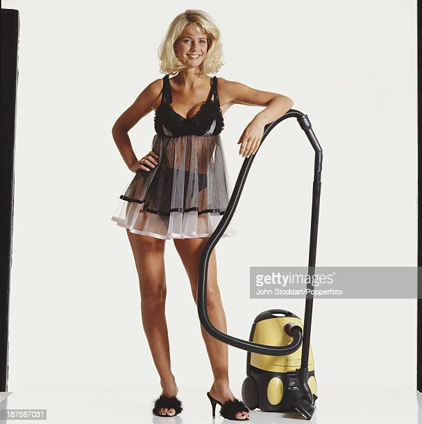 Swedish television presenter Ulrika Jonsson poses with a vacuum cleaner 1996