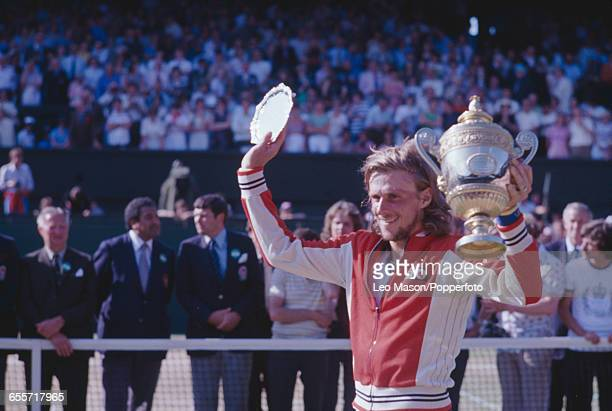 Swedish tennis player Bjorn Borg pictured lifting the Gentlemen's Singles Trophy and plate after winning the final of the Men's Singles tournament...