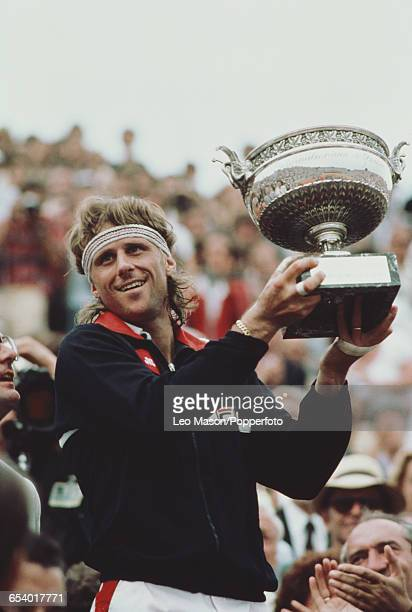 Swedish tennis player Bjorn Borg pictured raising the Coupe des Mousquetaires trophy in the air in celebration after defeating Ivan Lendl in the...