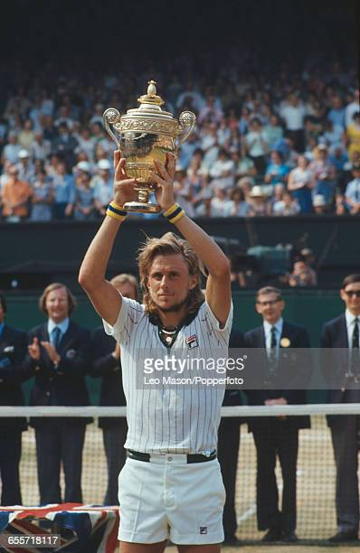 Swedish tennis player Bjorn Borg pictured raising the Gentlemen's Singles Trophy in the air after defeating Ilie Nastase to win the final of the...