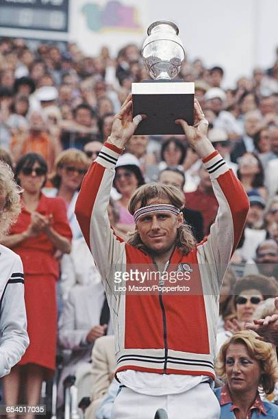 Swedish tennis player Bjorn Borg pictured raising the trophy in the air in celebration after defeating Vitas Gerulairis in the final of the Men's...