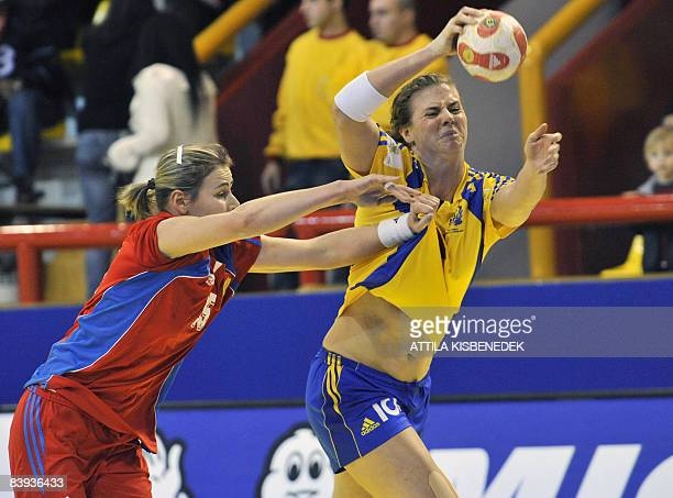 Swedish Teresa Utkovic fights for the ball with Russian Maya Petrova during the 8th Women's Handball European Championships match on December 6 2008...