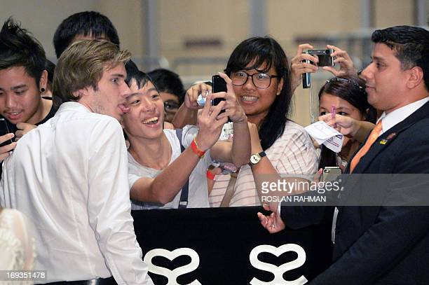 Swedish video game commentator Felix Kjellberg aka PewDiePie poses for a picture with a fan as he arrives to attend the Singapore Social Star Awards...