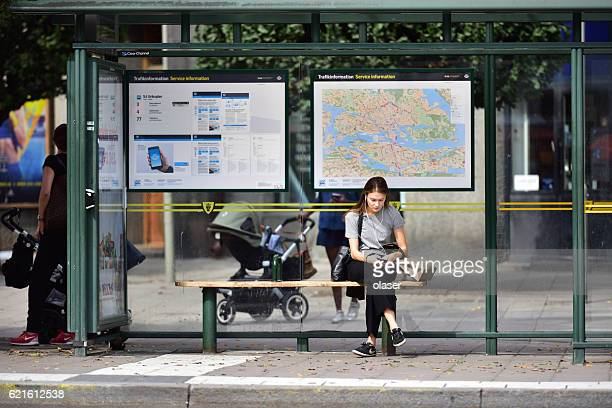 Swedish young woman at bus stop, using mobile smart phone
