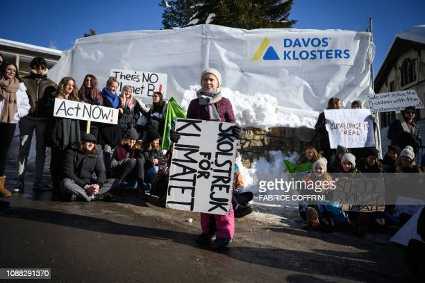 Swedish youth climate activist Greta Thunberg holds a placard next to students during a School strike for climate held on the sidelines of the World...