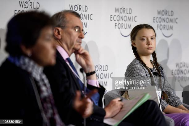 Swedish youth climate activist Greta Thunberg looks on prior to delivering a speech next to moderator Christiana Figueres and Governor of the Bank of...
