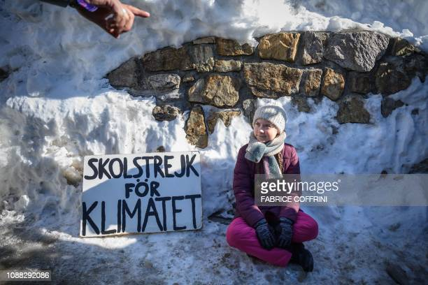 TOPSHOT Swedish youth climate activist Greta Thunberg sits next to a placard reading school strike for climate on the sidelines of the World Economic...
