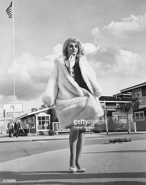 Swedishborn actor and singer AnnMargret wears a fake fur coat while walking on a sidewalk in a still from the film 'Kitten With a Whip'