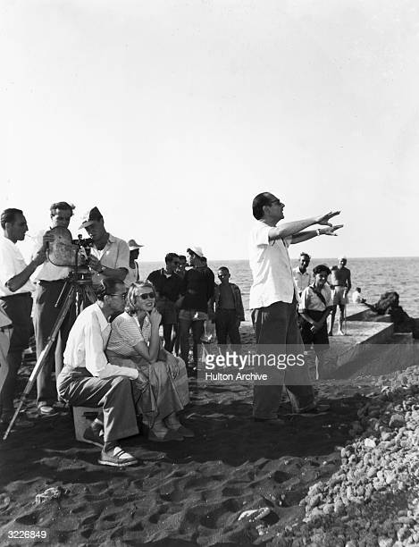 Swedish-born actor Ingrid Bergman sits with an unidentified crew member as her husband, Italian film director Roberto Rossellini , stands with his...