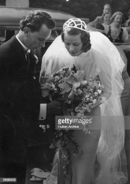 Swedish-born actor Ingrid Bergman with her first husband, dentist Dr. Petter Lindstrom, at their wedding. They hold the bridal bouquet together.