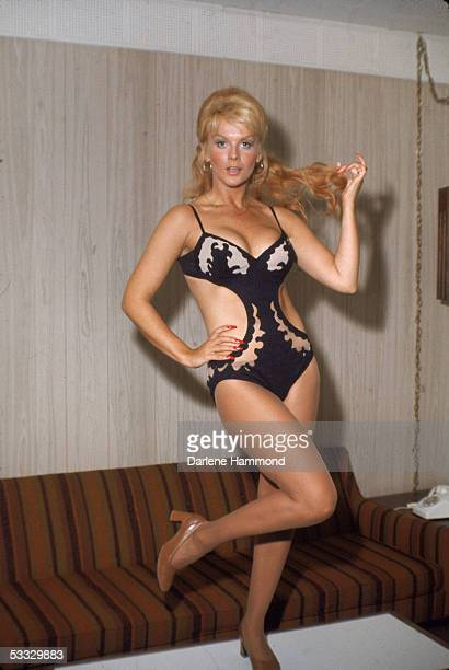 Swedishborn actress and dancer AnnMargret stands on a coffee table twirling her hair wearing a cutaway onepiece bathing suit 1970s