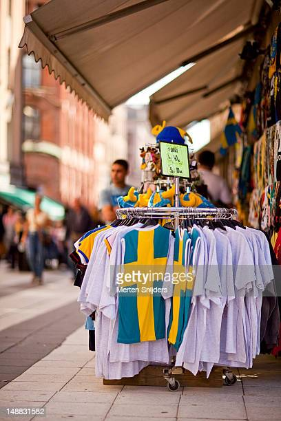 swedish-themed tourist shop on drottninggatan with national flag shirts on display. - merten snijders stockfoto's en -beelden