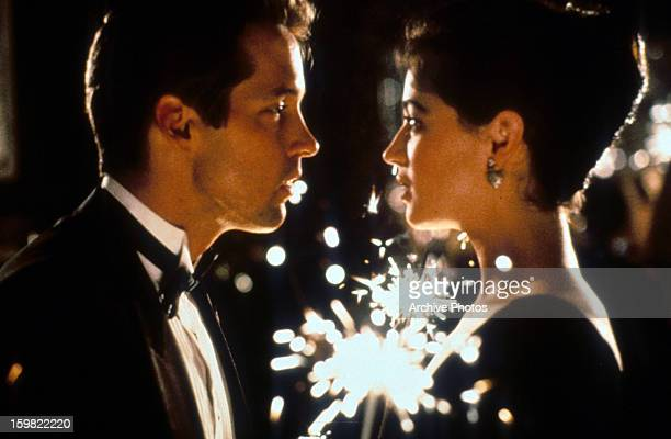 DB Sweeney and Moira Kelly looking passionate into one an others eyes as fireworks go off in the background in a scene from the film 'The Cutting...