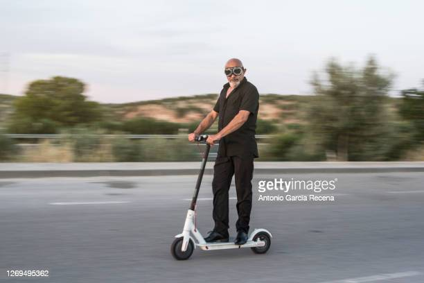 sweep photo of mature man driving an electric scooter, sweeping effect for green vehicle promotion - electric scooter stock pictures, royalty-free photos & images
