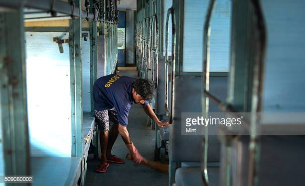 Sweeper cleaning the empty rackes of a train at Dadar on February 24 2015 in Mumbai India