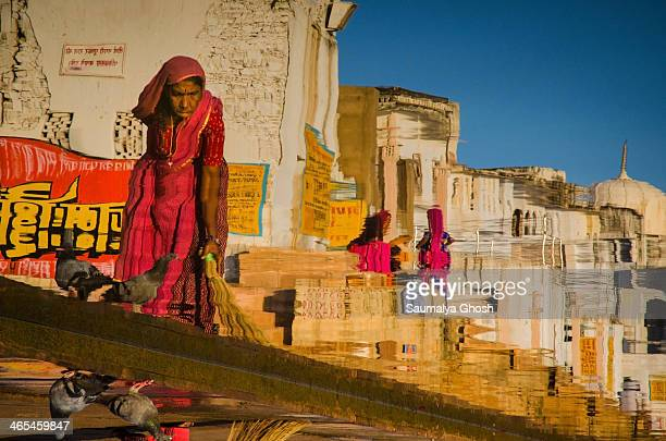 CONTENT] A sweeper is working at one of the Pushkar ghats in the morning This photograph shows her reflection on the water of the holy lake
