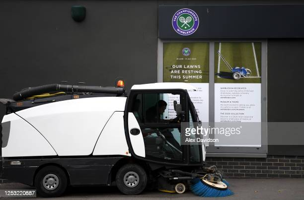 A sweeper passes a sign saying 'Our Lawns are resting this summer' at The All England Tennis and Croquet Club on June 29 2020 in Wimbledon England...