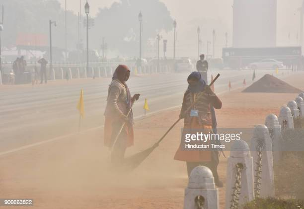 Sweepers clean the road during smog and foggy weather at Rajpath on January 18 2018 in New Delhi India