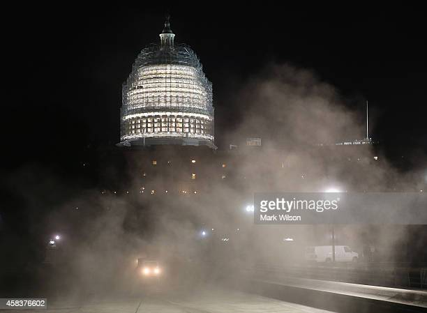 Sweepers stir up dust as they clean the reflecting pool in front of the US Capitol that is covered in scafollding for repairs November 4 2014 in...