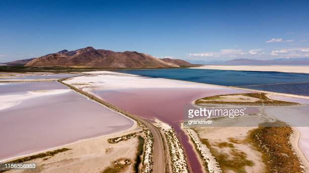a sweeping drove view of the pink and white salt reservoirs near antelope island near the great salt lake in utah - great salt lake stock pictures, royalty-free photos & images