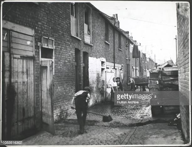 Sweeping Lynton Mews a slum area of Bermondsey South London England 18th September 1919