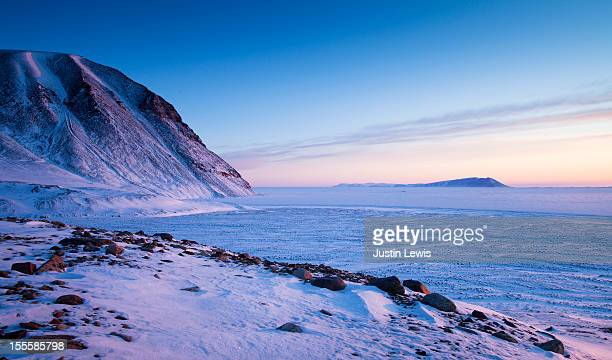 Sweeping view of sea ice and mountains at sunset