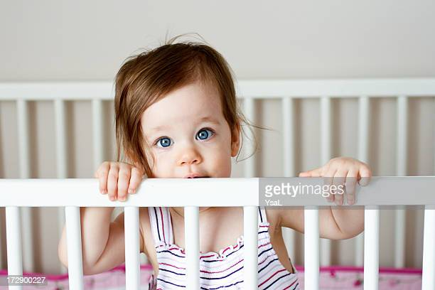 Sweet baby girl looking out over her crib rail
