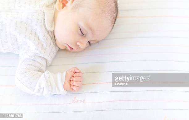 sweet baby sleeping in a crib - crib stock pictures, royalty-free photos & images