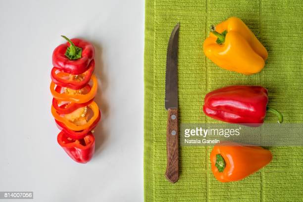 Sweet bell peppers and knife on white table