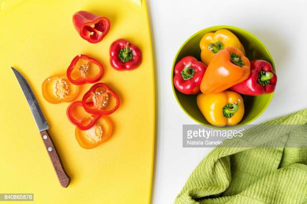 sweet bell peppers in bowl and on cutting board - pepper vegetable stock pictures, royalty-free photos & images