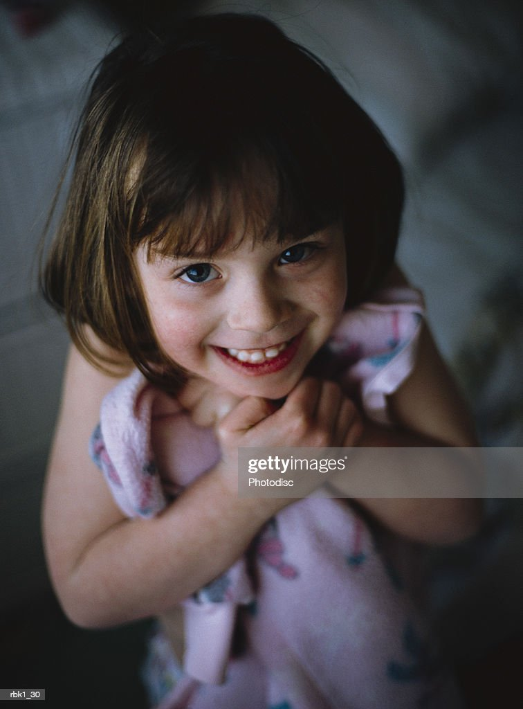 A sweet caucasian girl modestly clutches her blanket and giggles : Stockfoto