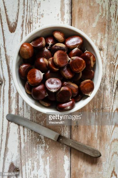 sweet chestnuts in a bowl and knife - castanhas imagens e fotografias de stock