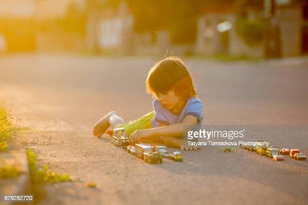 Sweet child, boy, playing with car toys on the street in village on sunset, summertime