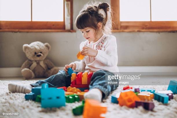 sweet child playing with plastic blocks - toy stock pictures, royalty-free photos & images